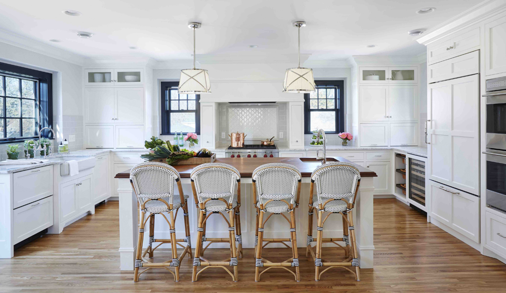 White kitchen with rattan kitchen stools. Kitchen with drum pendant lights over white kitchen island with wooden countertop