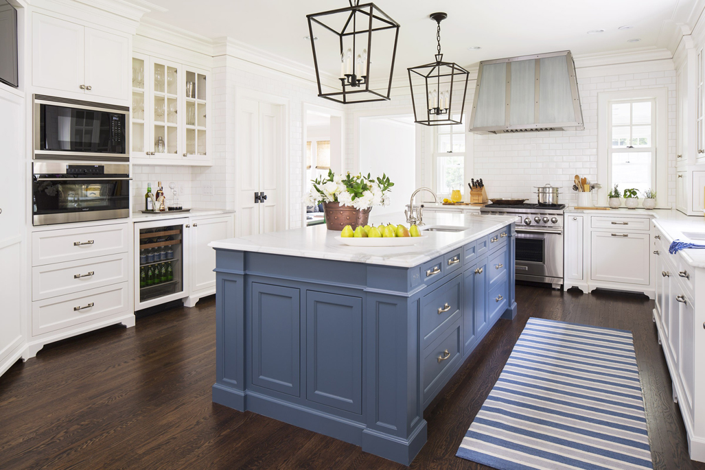 White kitchen with dark wood floors. Kitchen with box pendant lights over blue kitchen island with white marble countertop