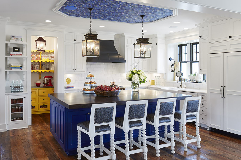 White kitchen with white bar stools and reclaimed oak flooring. Kitchen with lantern pendant lights over navy kitchen island with dark wood countertop