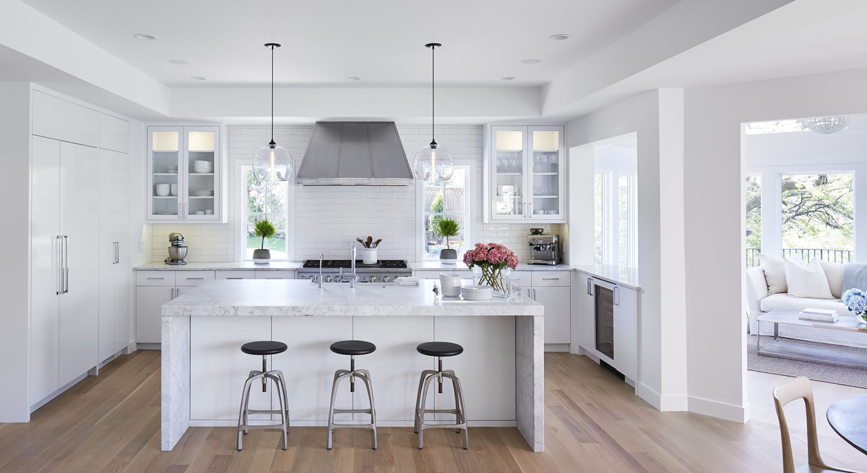 White kitchen with dark laminate wood floor texture. Kitchen with bar stools with glass pendant lights over white kitchen island with white marble countertop