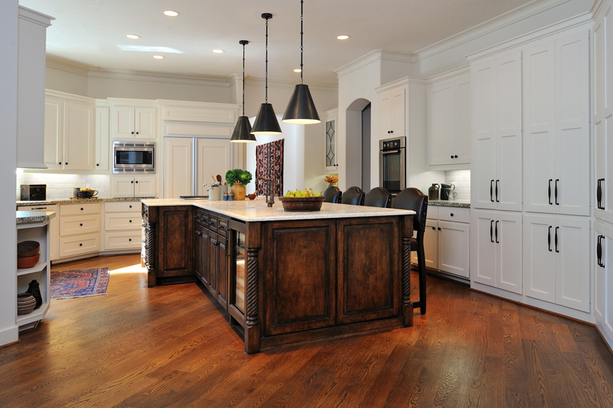 White kitchen with dark wood island with hickory wood floors and black pendant lights