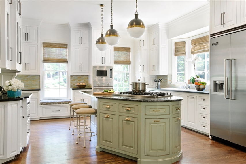 White kitchen with light wood floors. Kitchen with bar stools with white pendant lights fixture over green kitchen island with black marble countertop