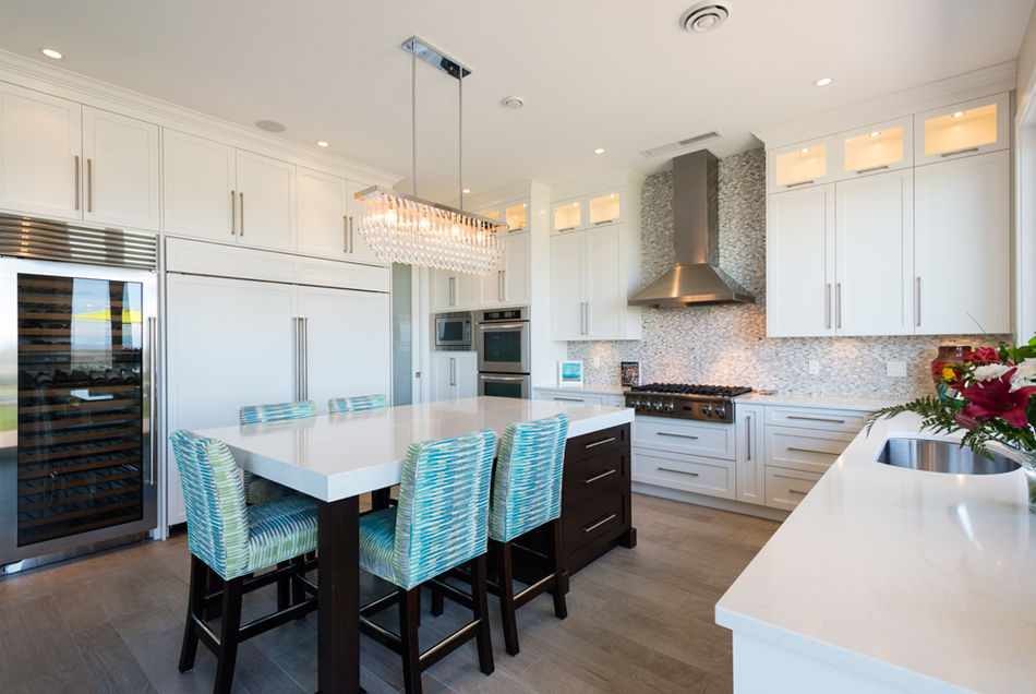 White kitchen with blue accents. Kitchen with linear crystal chandelier over dark kitchen island with white laminate countertop