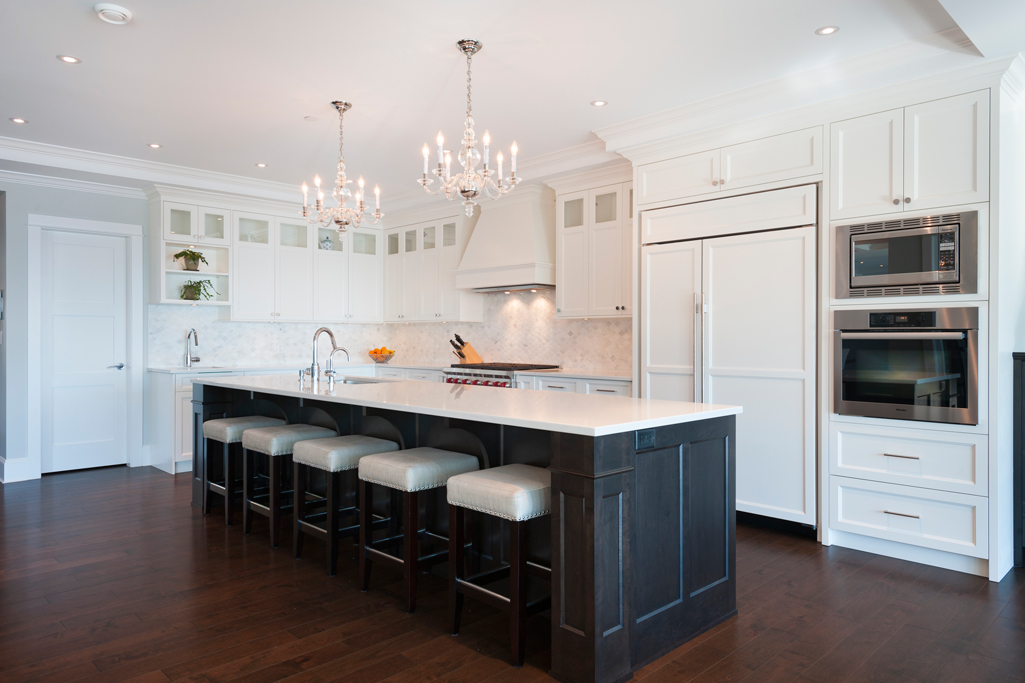 White kitchen with white backsplash and dark wood floors. Kitchen with mini candle chandelier over black kitchen island with white laminate countertop