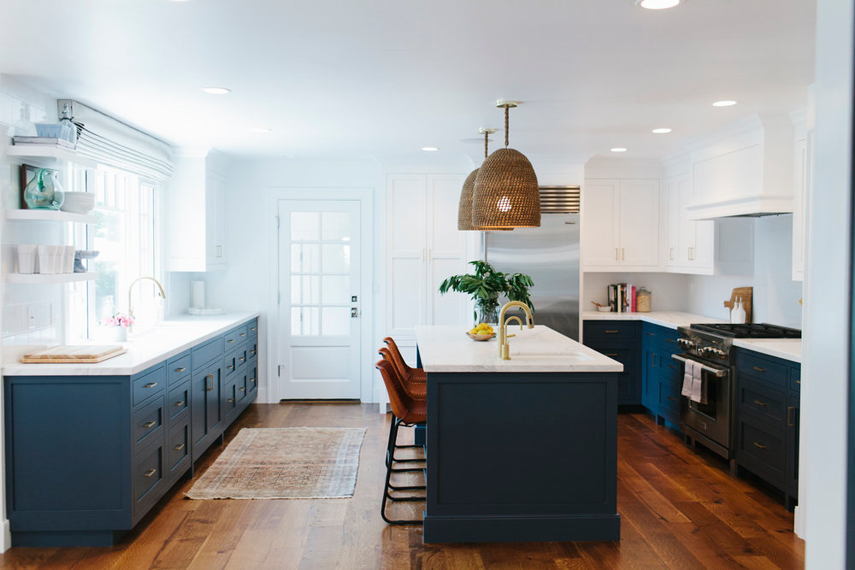 White kitchen with navy accents and hardwood floors. Kitchen with unique dome pendant lights over navy kitchen island with white laminate countertop