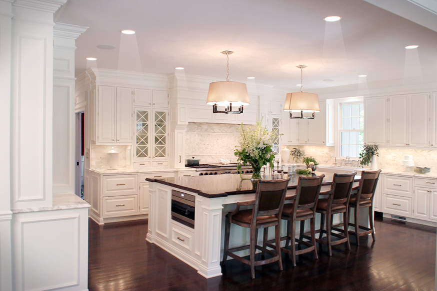 White kitchen with glossy solid dark hardwood floors. Kitchen with drum shade chandeliers over white kitchen island with dark chocolate countertop