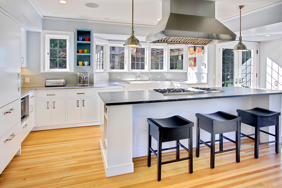 White kitchen with black wooden bar stools and light wood flooring. Kitchen with modern pendant lights over white kitchen island with black laminate countertop