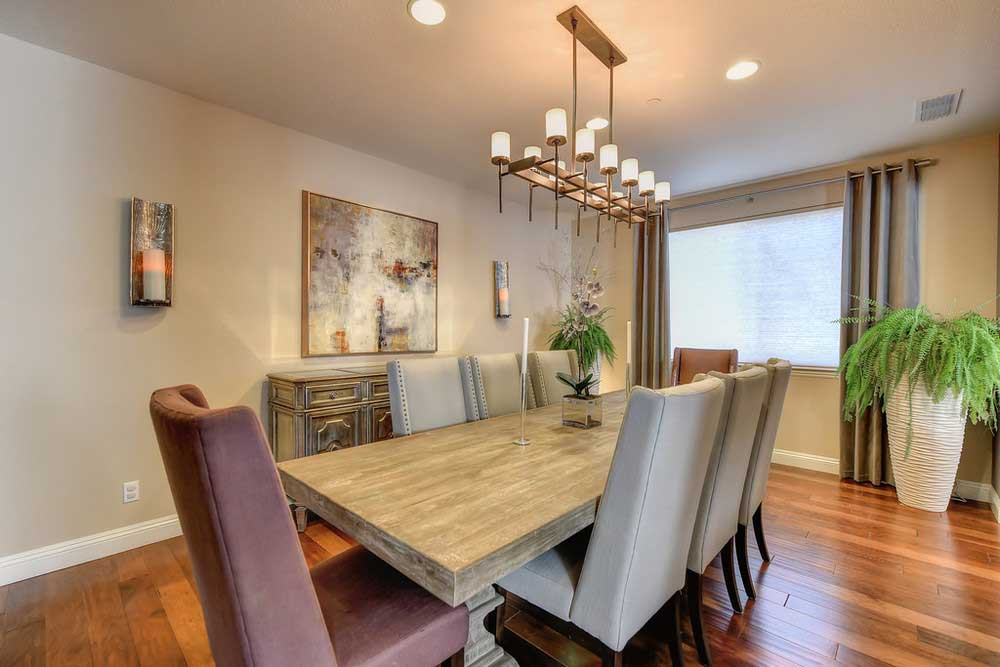 gray dining room with wall sconces and candle pendant light
