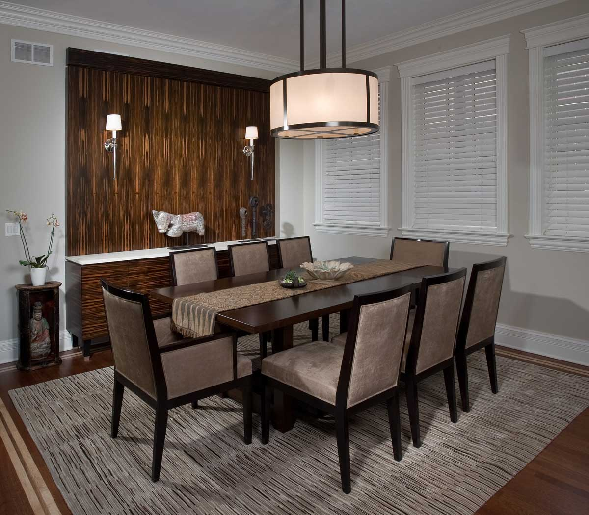 dining room with wall sconces and drum pendant light