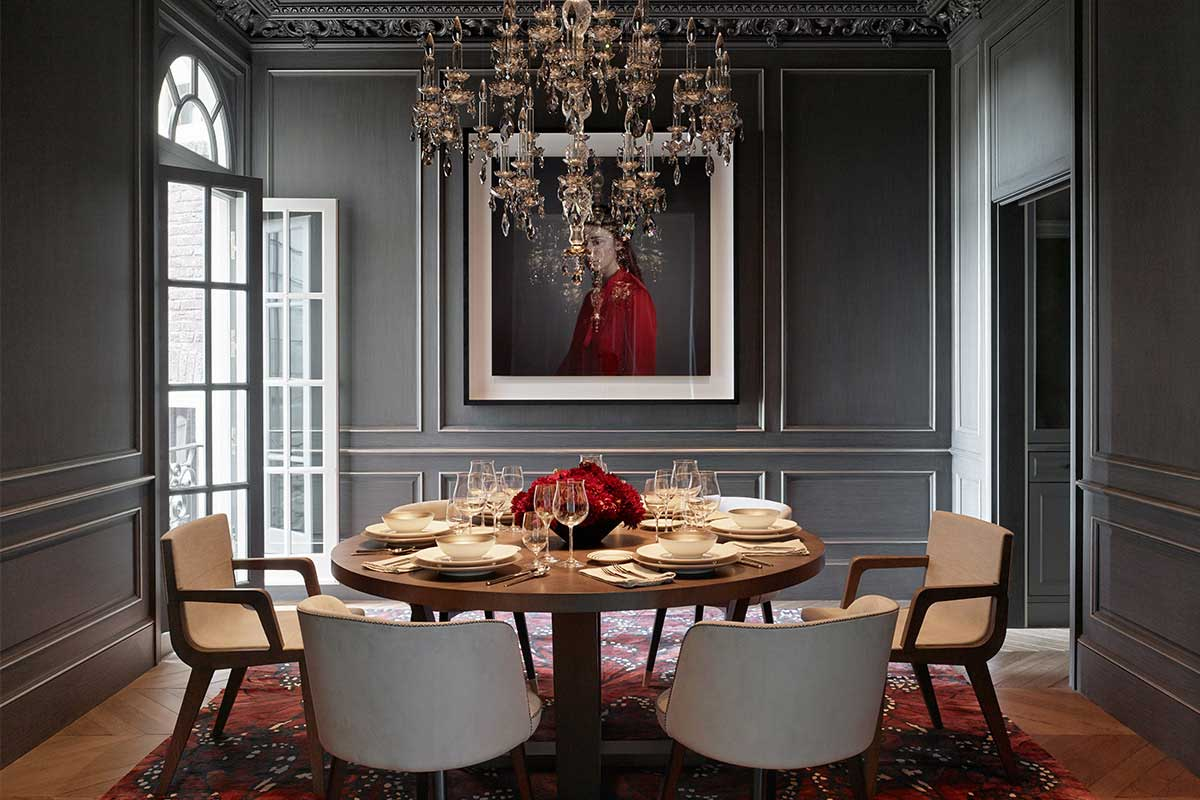 gray dining room with round table and candle chandeliers