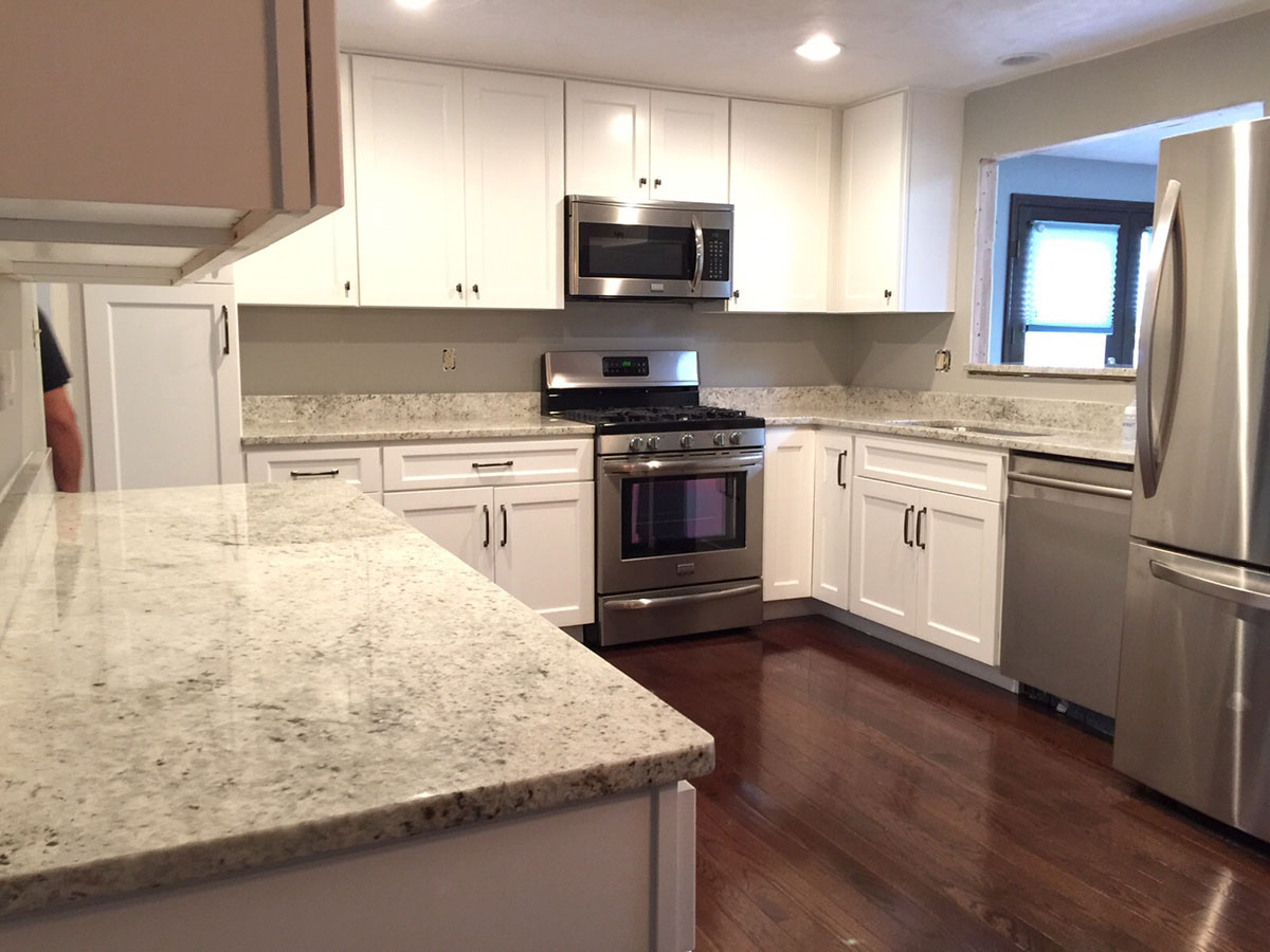 Small white kitchen with colonial white granite countertops