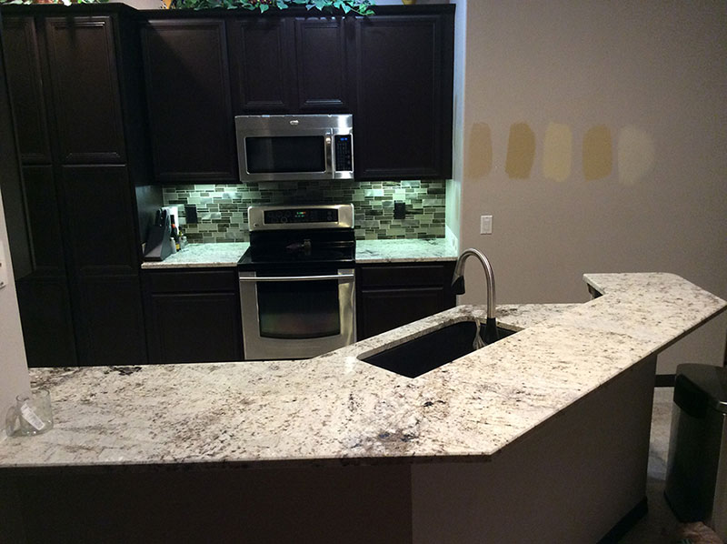 Black cabinets with white galaxy granite countertops