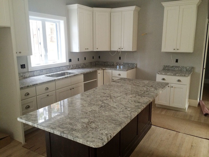 White kitchen cabinets with thunder white granite countertops