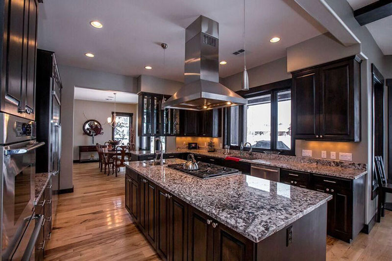 Dark kitchen cabinets and white wave granite countertops