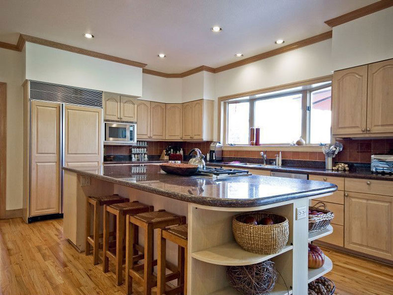 Traditional kitchen with tan brown granite countertops and creams cabinets
