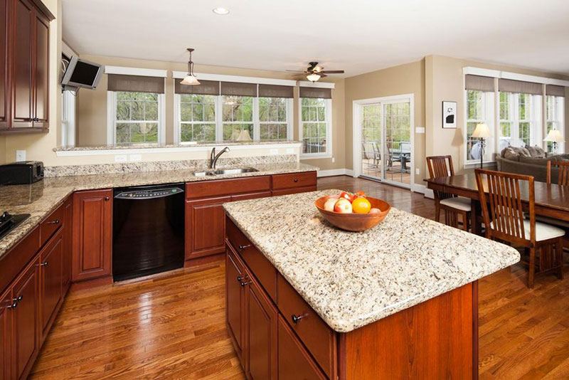 Open plan kitchen design with bianco antico countertops