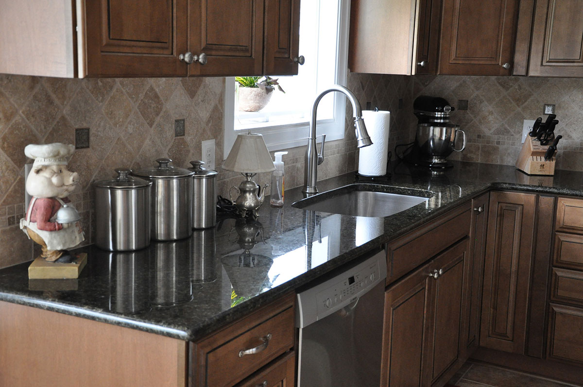 Dark brown cabinets with uba tuba granite