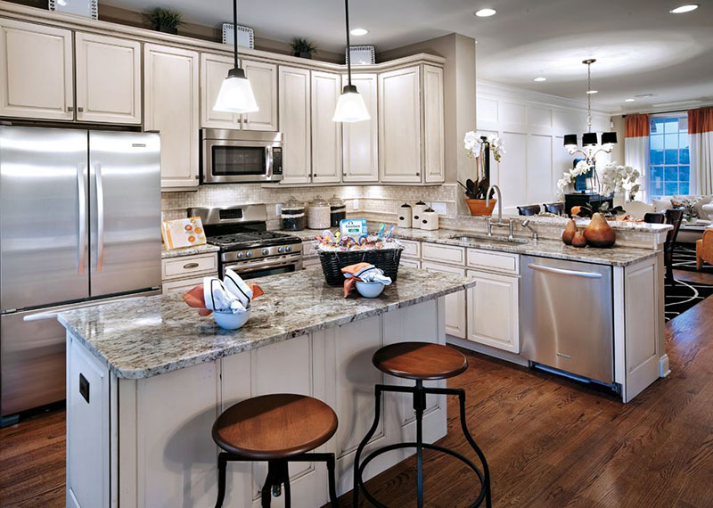Traditional white kitchen design with bianco antico granite countertops