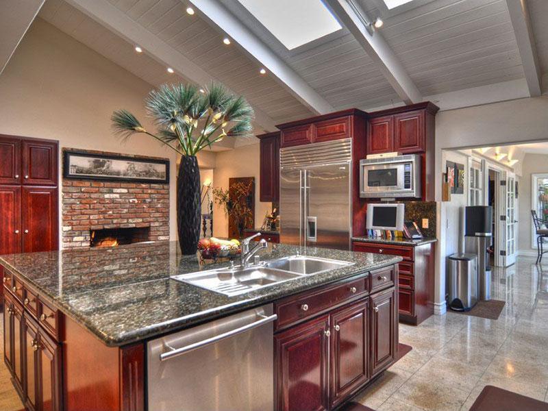 Large kitchen island with uba tuba granite countertops